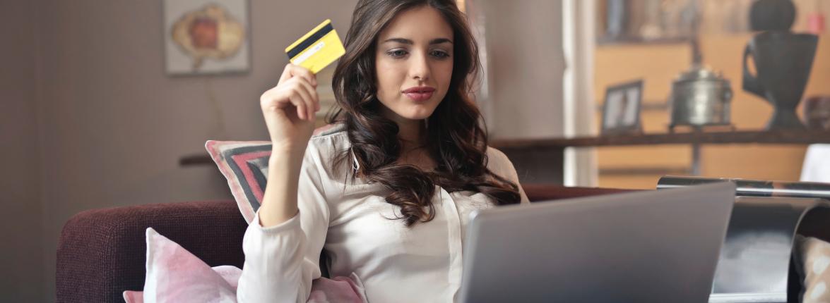 Eine Dame schaut auf ihr Notebook und hält in der Hand eine Kreditkarte